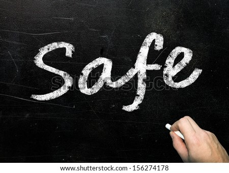 The word Safe handwritten in white chalk on a used blackboard