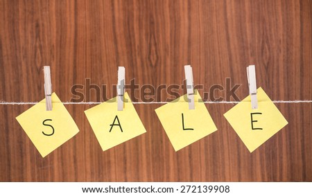 The word sale hanging with clothespins. Conceptual image of price discount and retail sales. - stock photo
