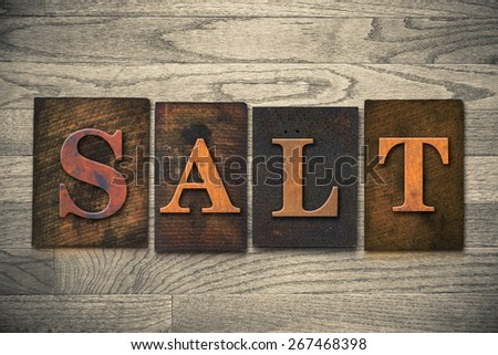 "The word ""SALT"" theme written in vintage, ink stained, wooden letterpress type on a wood grained background."