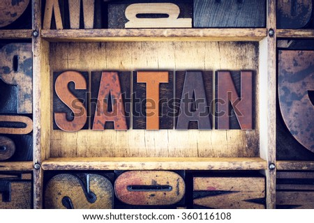 "The word ""Satan"" written in vintage wooden letterpress type."