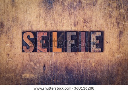 """The word """"Selfie"""" written in dirty vintage letterpress type on a aged wooden background. - stock photo"""