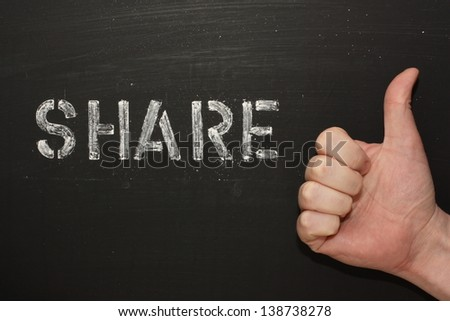 The word Share on a blackboard next to a hand giving the thumbs up gesture - stock photo