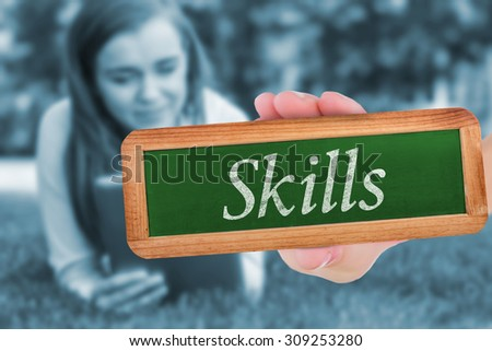 The word skills and hand showing chalkboard against university student lying and using tablet pc - stock photo