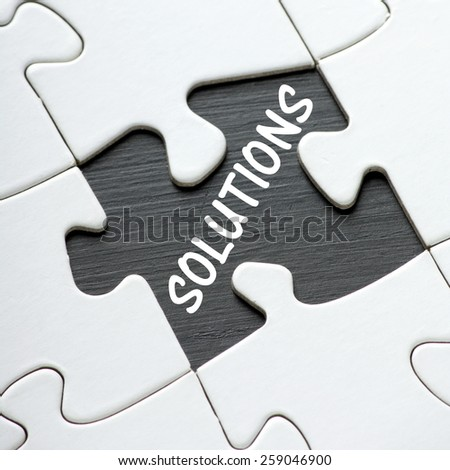 The word Solutions written in the space of a missing piece from a jigsaw puzzle as a concept for problem solving - stock photo