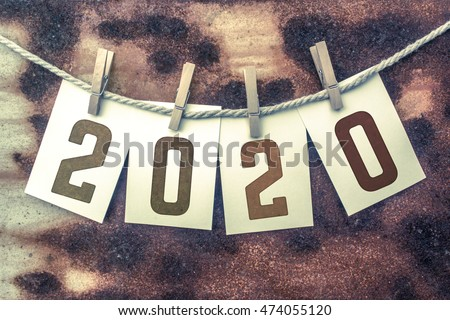 "The word ""2020"" stamped on cards and pinned to an old piece of twine over a rusted metal background."