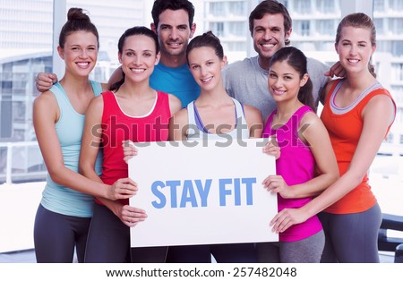 The word stay fit against fit smiling people holding blank board - stock photo