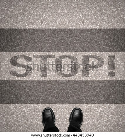 The word stop on zebra crossing with business man shoes, overhead view - stock photo