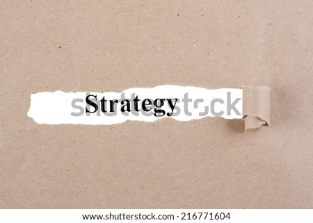The word strategy written on white paper and on top of torn cardboard - stock photo