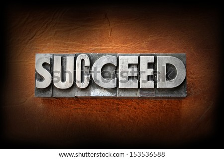 The word succeed made from vintage lead letterpress type on a leather background. - stock photo