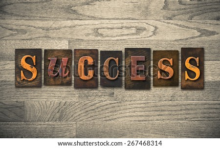 "The word ""SUCCESS"" theme written in vintage, ink stained, wooden letterpress type on a wood grained background. - stock photo"