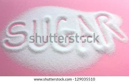 The word sugar written into a pile of white granulated sugar with a pink background - stock photo