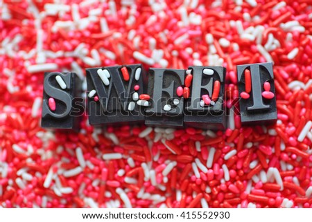 The word 'sweet' in metal type on a pink and white candy sprinkles background - stock photo