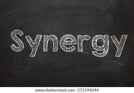 The word Synergy handwritten with white chalk on a blackboard - stock photo