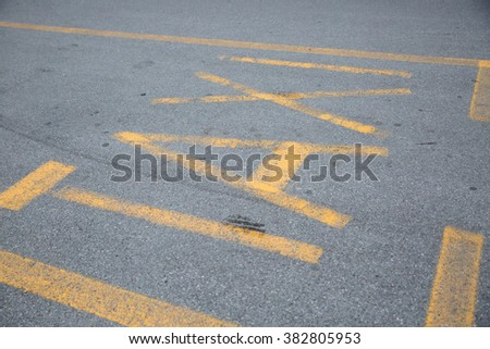 "The word ""Taxi"" written in bright yellow on gray dirty pavement."