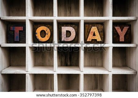 """The word """"TODAY"""" written in vintage ink stained wooden letterpress type in a partitioned printer's drawer. - stock photo"""