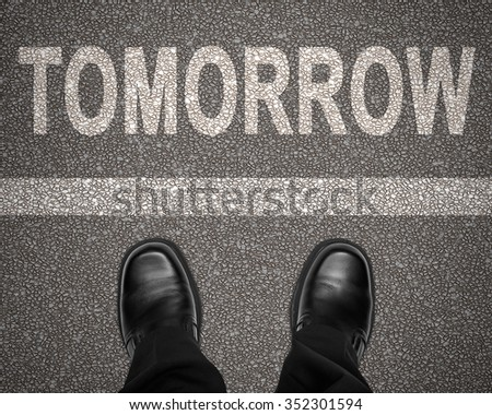 The word tomorrow with stripe on road and business man shoes standing still, top view , looking down - stock photo