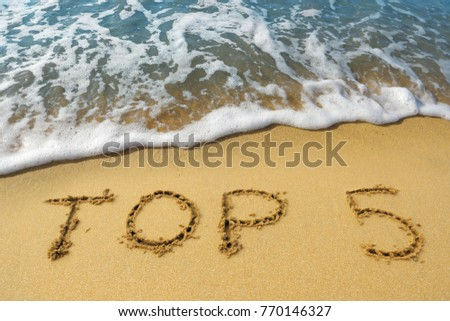 "The word ""top 5"" is written on the golden sand of the beach by the sea. Concept - the five best beaches, tours or ways to relax in the south."