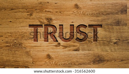 The word TRUST Engraved in Wooden Background. - stock photo