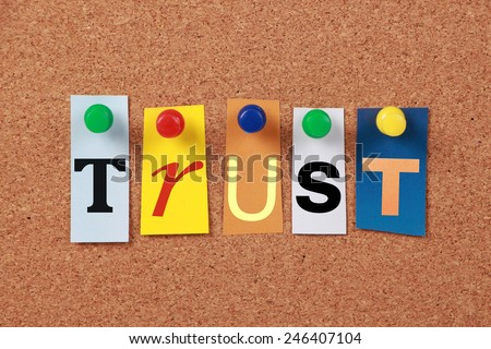 The word Trust in cut out magazine letters pinned to a cork board. - stock photo
