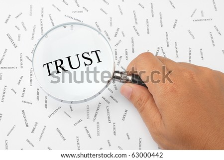 The word, TRUST is magnified. - stock photo