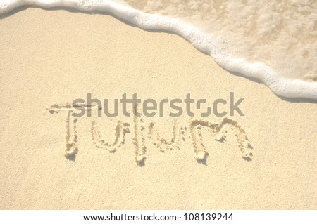The Word Tulum Written in the Sand on a Beach - stock photo