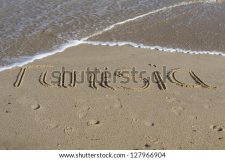 The word Tunisia written in sand with waves lapping at the beach