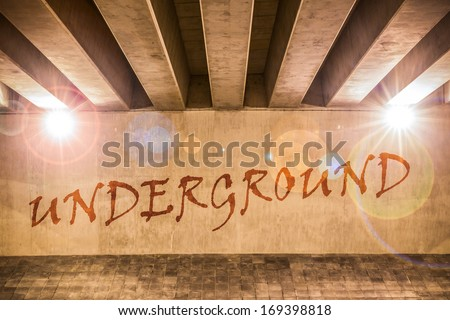 The word underground painted as graffiti on the support column of an overpass - stock photo