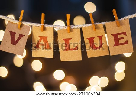 The word VALUE printed on clothespin clipped cards in front of defocused glowing lights. - stock photo