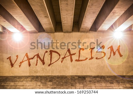 The word vandalism painted as graffiti on the support column of an overpass - stock photo