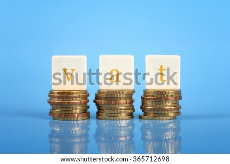 The word VAT on stacked coins, finance conceptual