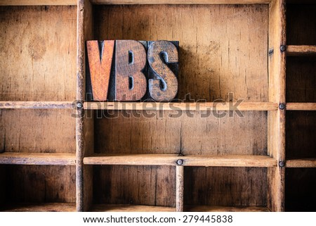 The word VBS written in vintage wooden letterpress type in a wooden type drawer. - stock photo