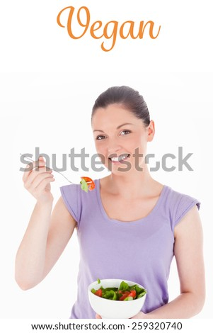 The word vegan against attractive woman eating a bowl of salad while standing - stock photo