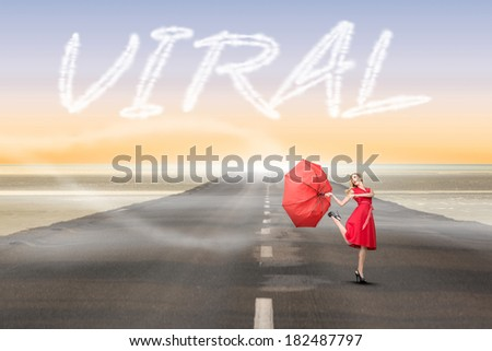 The word viral and beautiful woman posing with a broken umbrella against road leading out to the horizon