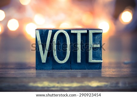 The word VOTE written in vintage metal letterpress type on a soft backlit background. - stock photo