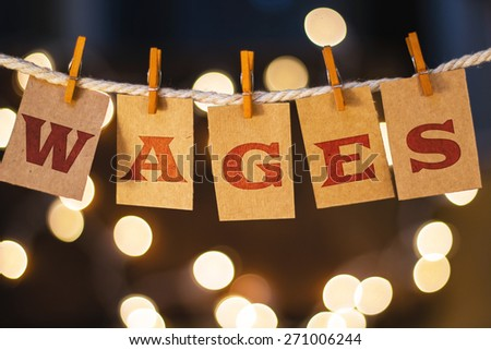 The word WAGES printed on clothespin clipped cards in front of defocused glowing lights. - stock photo