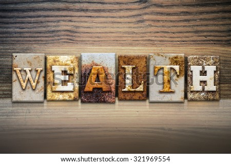 "The word ""WEALTH"" written in rusty metal letterpress type sitting on a wooden ledge background. - stock photo"