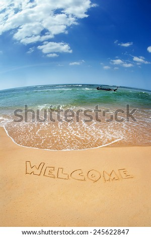 "The word ""Welcome"" written on the sand against the sea. Phuket island, Thailand"