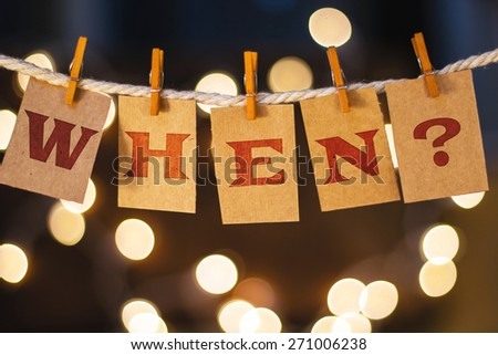 The word WHEN? printed on clothespin clipped cards in front of defocused glowing lights. - stock photo