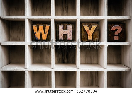 """The word """"WHY"""" written in vintage ink stained wooden letterpress type in a partitioned printer's drawer. - stock photo"""
