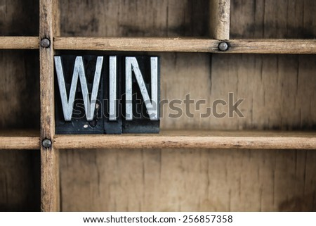 "The word ""WIN"" written in vintage metal letterpress type in a wooden drawer with dividers. - stock photo"
