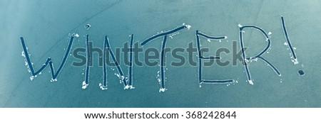The word winter written on a frozen car windscreen - stock photo