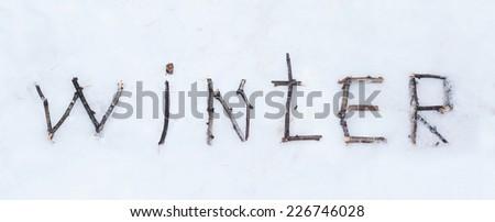 The word winter written with broken wooden sticks on snow background - stock photo