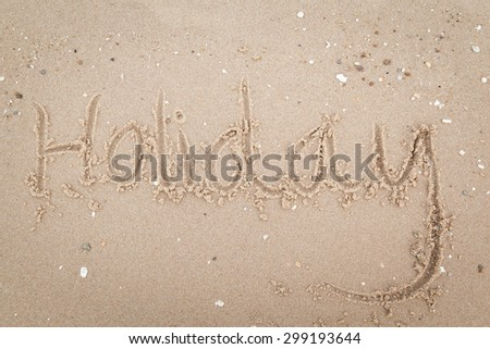 "The word with hashtag ""holiday"" in the sand against the sea"