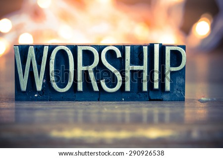 The word WORSHIP written in vintage metal letterpress type on a soft backlit background. - stock photo