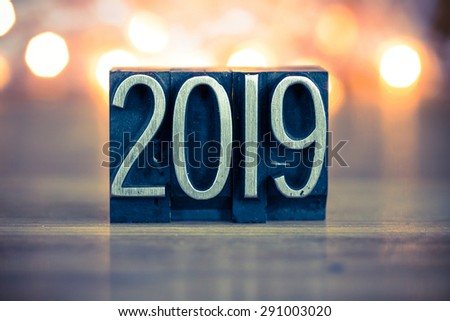 The word 2019 written in vintage metal letterpress type on a soft backlit background. - stock photo