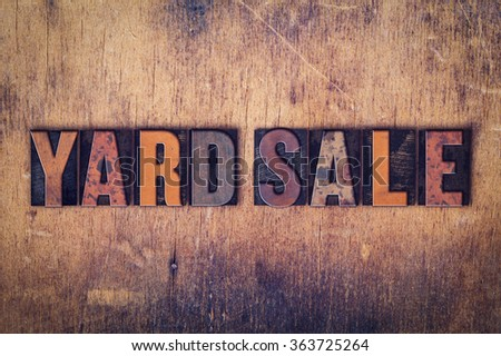 "The word ""Yard Sale"" written in dirty vintage letterpress type on a aged wooden background. - stock photo"