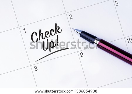The words Check Up written on a calendar planner to remind you an important appointment with a pen on isolated white background.  - stock photo