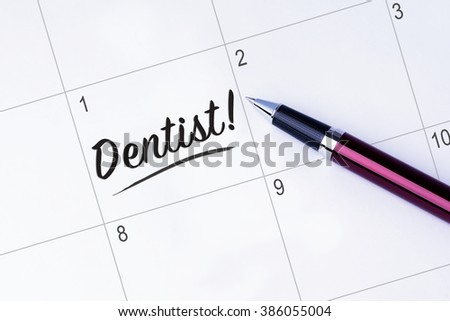 The words Dentist written on a calendar planner to remind you an important appointment with a pen on isolated white background.