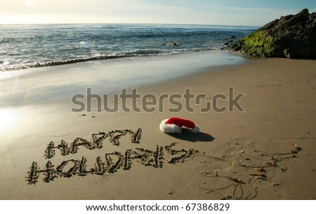 "the words ""Happy Holidays"" written in wet sand with a ""Santa Hat"" on a secluded beach in ""southern california"" with the tide of the pacific ocean and blue sky in the background - stock photo"