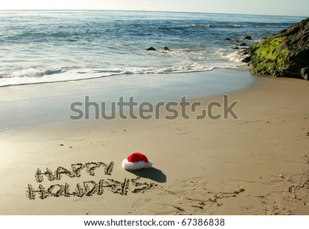 """the words """"Happy Holidays"""" written in wet sand with a """"Santa Hat"""" on a secluded beach in """"southern california"""" with the tide of the pacific ocean and blue sky in the background - stock photo"""
